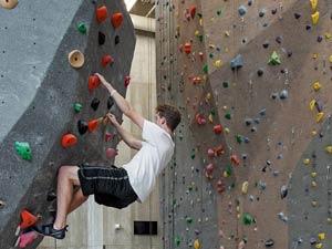 Student climbs rock wall at Outdoor Adventures Center